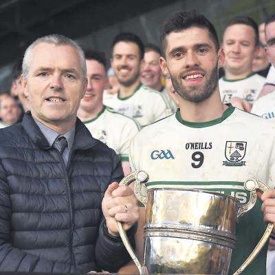 Aidan O'Sullivan is presented with the Sweeney Cup by county board vice chairman Seamus Tuohy.